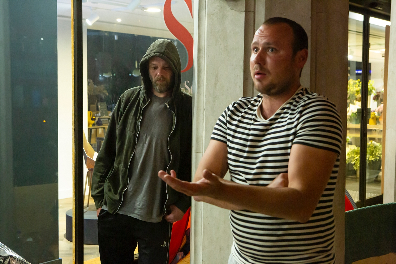 Two men, one in in a hoodie and one in a striped t-shirt, outside the Heals department store