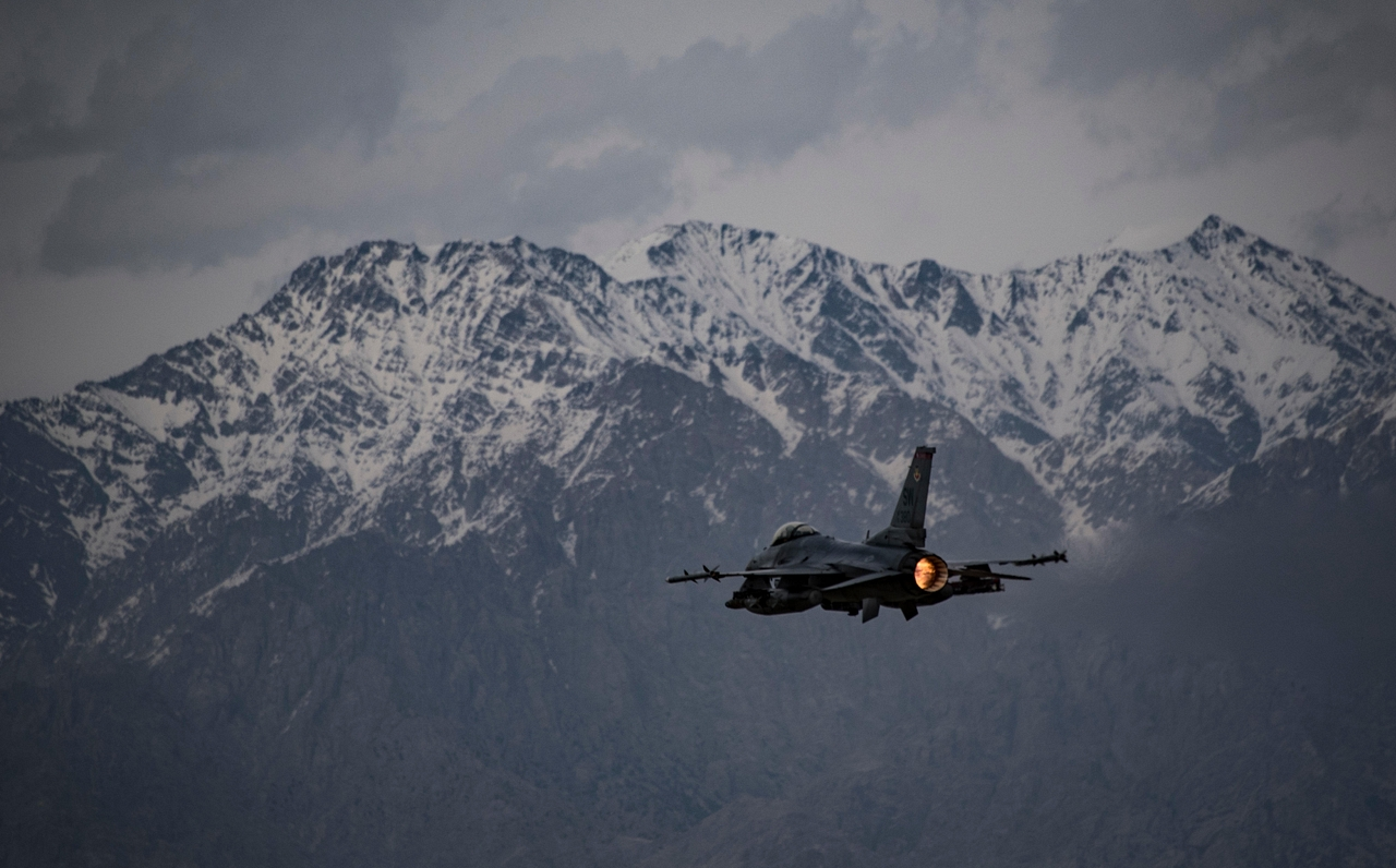 A fighter jet flying past snow-capped mountains