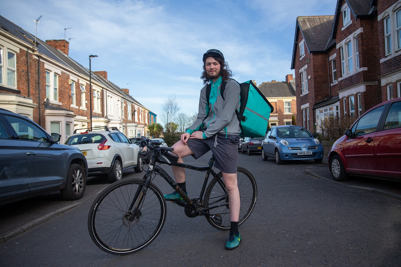 A young man wearing Deliveroo branded gear poses on his bike