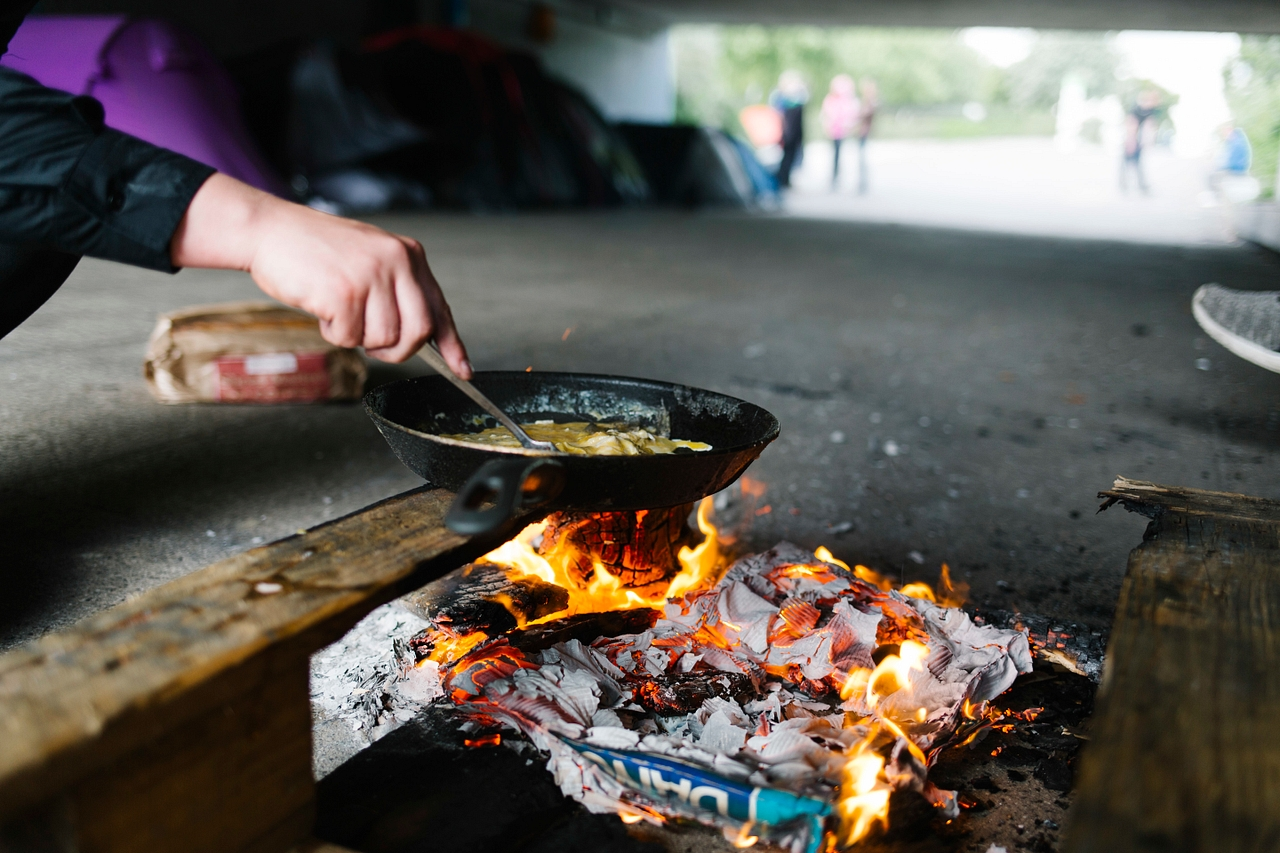 A homeless person cooks food over a makeshift fire in an underpass in Milton Keynes