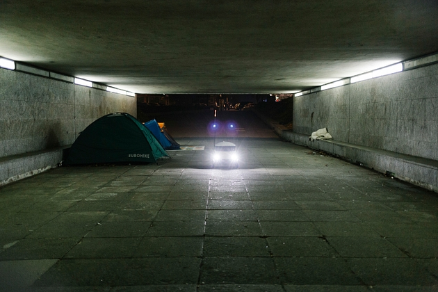 A food delivery robot passes through an underpass of Milton Keynes, near a homeless person's tent, 2018