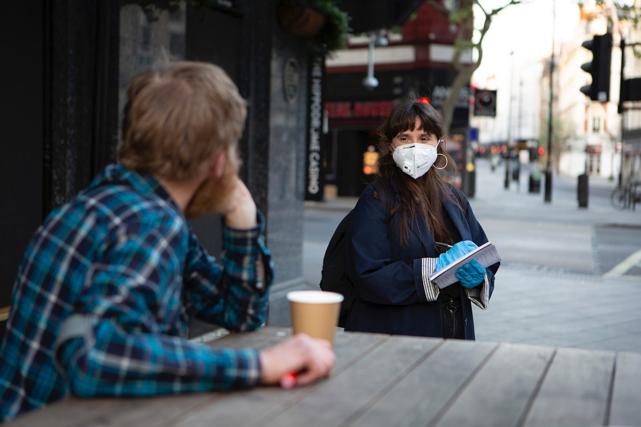 A man in a checked shirt talks to a woman in a protective mask and gloves as she takes notes
