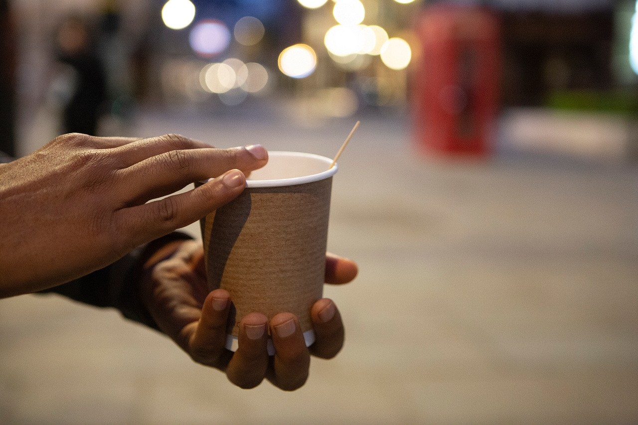 Hands holding a disposable coffee cup