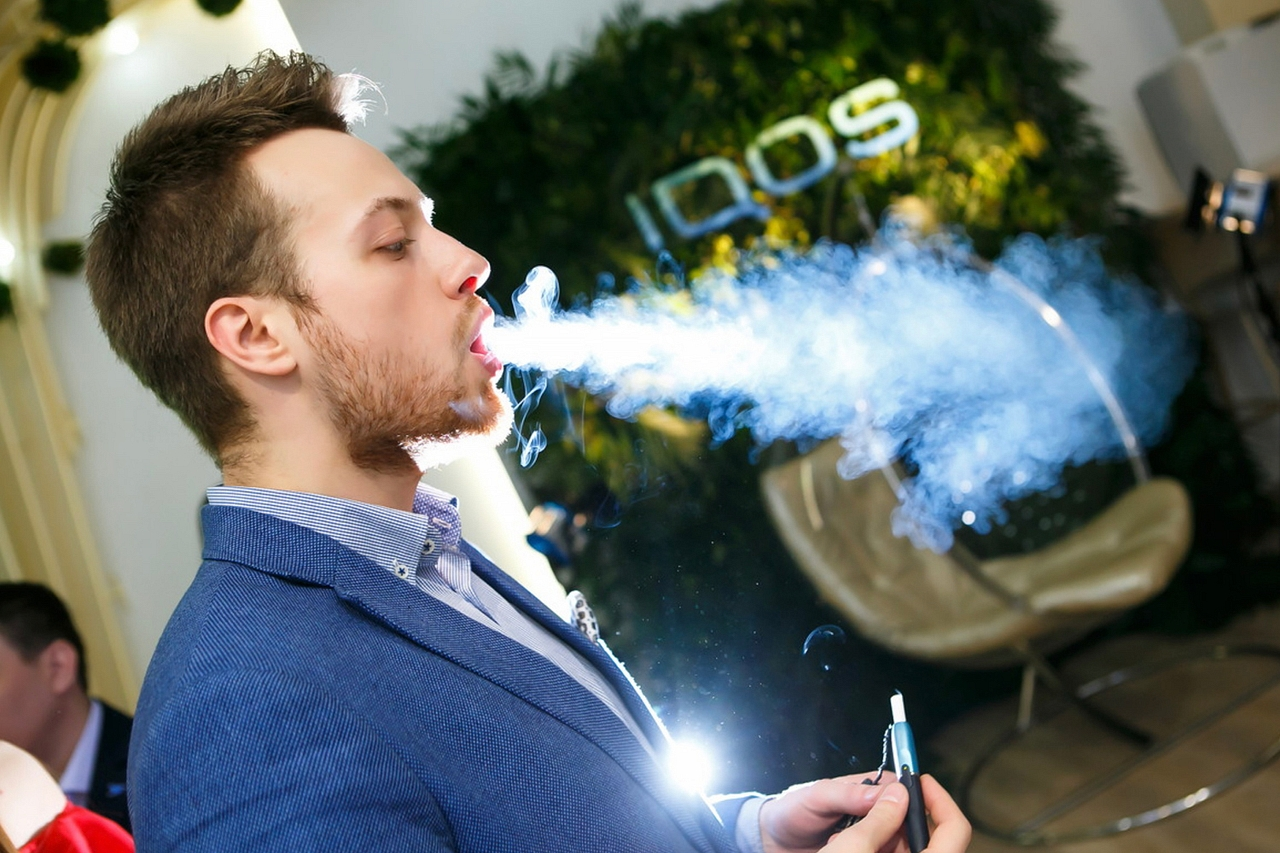 A man using an Iqos blows a stream of smoke
